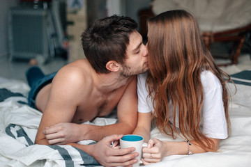 Young couple lying in bed and drinking coffee, kissing