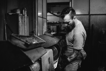 tattoed metal worker grinding metal plate in a workshop - black and white