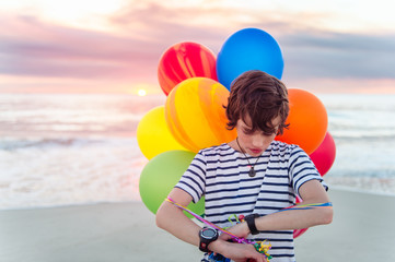 Boy with colorful balloons at the beach at sunset