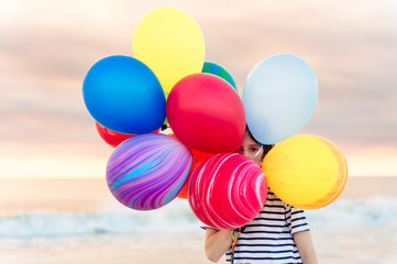 Boy hiding behind a large bunch of colorful balloons
