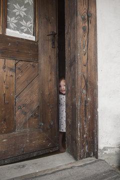 Little girl peeking through a wooden door