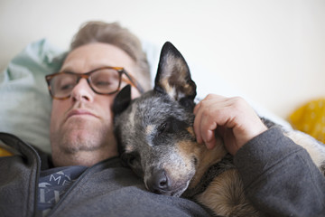 Middle aged man on his bed with his blue heeler dog