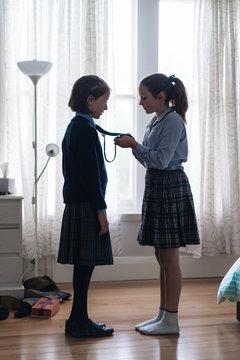 big sister helping with school uniform tie