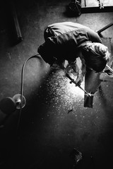 Black and white image of metal worker with cutting torch