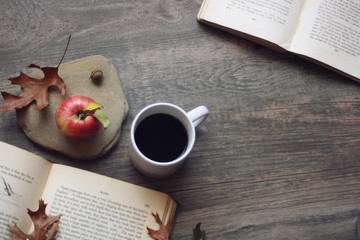 Autumn still life with apple, coffee, open books and leaves over rustic wooden background, copy space, horizontal