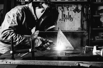 Black and white image of welder welding
