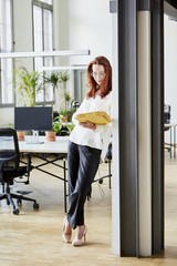 Full Length Of Businesswoman Reading File In Office