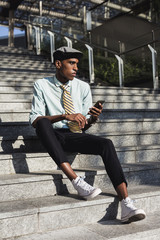 Stylish African American Businessman using mobile phone outdoor