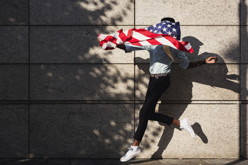 Young person running with an American flag