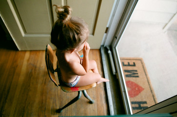 child sits in chair in front of door