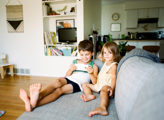 children sitting on couch watching video on smartphone