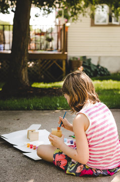 Young girl painting a wooden birdhouse