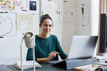 Smiling Graphic Designer At Desk In Creative Office