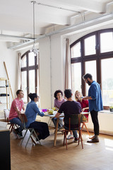 Designers Having Discussion At Conference Table