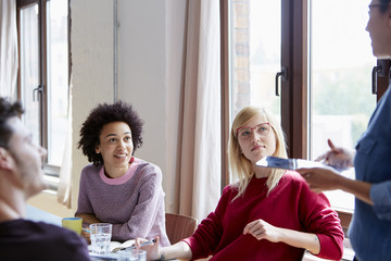 Businesswomen Listening To Colleague During Meeting