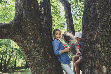 A Girl and A Boy Scouts Playing on Tree