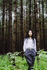 Beautiful woman in casual clothing stay in the dark forest