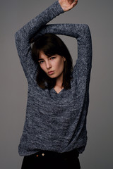 Young girl in grey pullover with arms up above head