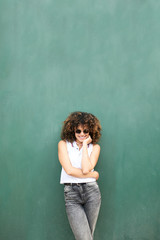 Cheerful mulatto woman in sunglasses on green background