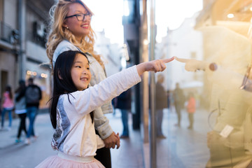 Happy young mother with her daughter looking at the window display