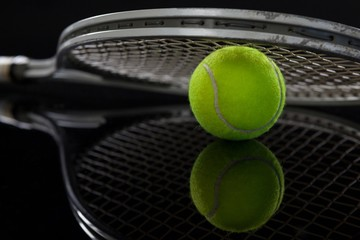 Close up of racket on fluorescent yellow tennis ball with