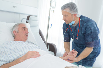 friendly male doctor hold patient hand in hospital room