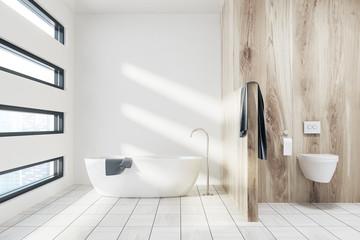 White bathroom with a tub, toilet