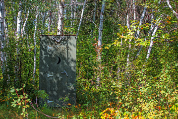 A primitive one stall wooden outhouse decorated with animal horns and a moon shaped cutout on the door surrounded by a forest of trees in a summer afternoon
