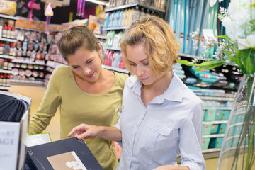 two female customers selecting haircare products in drugstore