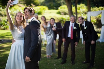 Couple taking selfie with guests during wedding