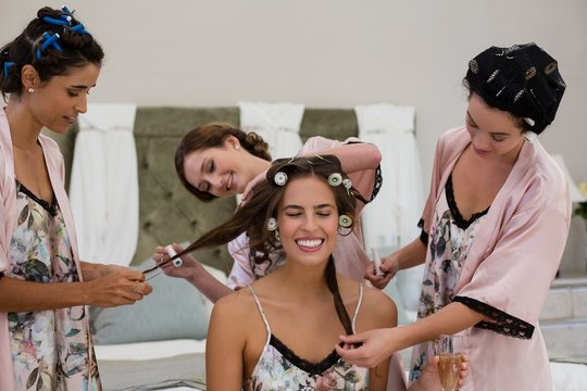 Bridesmaid assisting bride in getting ready