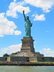 The Statue of Liberty in New York City with a blue sky background