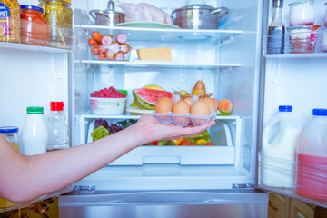 Open refrigerator filled with food. hands holding a box with eggs