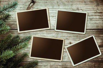 Christmas background - Blank photo frame paper with fir tree decorating rustic elements on vintage wood table. Creative Flat layout and top view composition with border and copy space design.