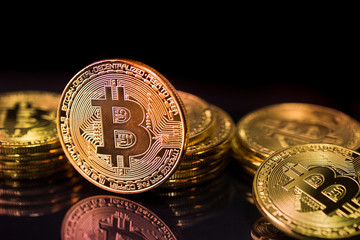 Bitcoins and New Virtual money concept.Stack of Many gold bitcoins on reflective surface.Golden coin with icon letter B.Mining or blockchain technology for cryptocurrency.
