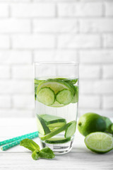 Delicious refreshing water with mint and cucumber in glass on light background