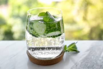 Delicious refreshing water with mint and cucumber in glass on table