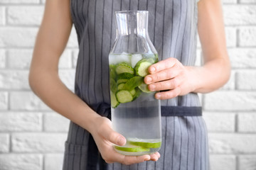 Young woman holding bottle of delicious refreshing water with mint and cucumber, closeup