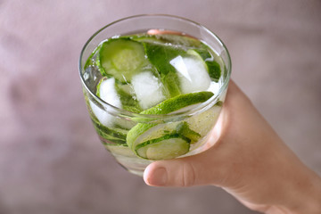 Female hand holding glass of delicious refreshing water with mint and cucumber on blurred background