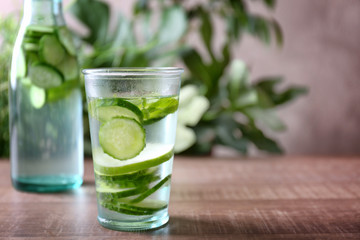 Delicious refreshing water with mint and cucumber in glass on wooden table