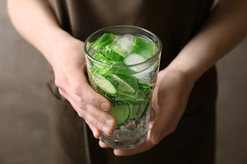 Young woman holding glass of delicious refreshing water with mint and cucumber, closeup