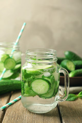 Delicious refreshing water with mint and cucumber in mason jar on wooden table
