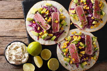Tacos with tuna steak and fresh vegetables close-up. horizontal top view