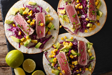 Mexican tacos with tuna, red cabbage, corn, avocado and onions close-up. horizontal top view