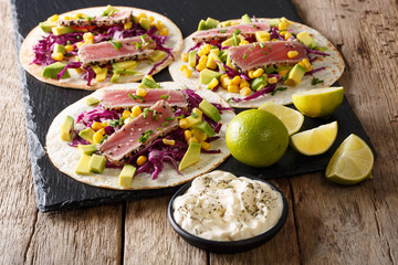 Delicious fish takos with fried tuna fillets, corn, red cabbage, lime and avocado close-up. horizontal