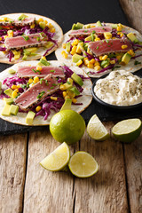 Appetizing food: tacos with tuna, sesame, corn, red cabbage and avocado close-up. vertical