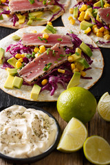 Delicious food: fish tortillas with tuna, sesame, corn, cabbage and avocado close-up. vertical
