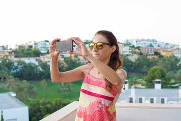 smiling woman taking a photo with mobile in the terrace