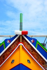 The bow of a brightly painted traditional Dghajsa boat, Bigibba, Malta.