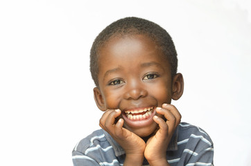 Laughing African child holds his head whilst thinking (Africa ethnicity black boy)